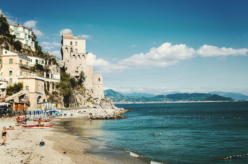 Cetara, Italy - October 2, 2013: Cetara small beach village on the Amalfi Coast, LA beach is defended by an ancient Saracen tower. Bathers on the beach on a warm October day. In the background you can see the city of Salerno Architecture Beauty In Nature Blue Building Exterior Built Structure City Cloud Cloud - Sky Coastline Day Nature Outdoors Scenics Sky Tourism Town Tranquility Travel Destinations Water