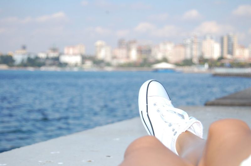 Low Section Of Woman Resting At Promenade Sunny Day