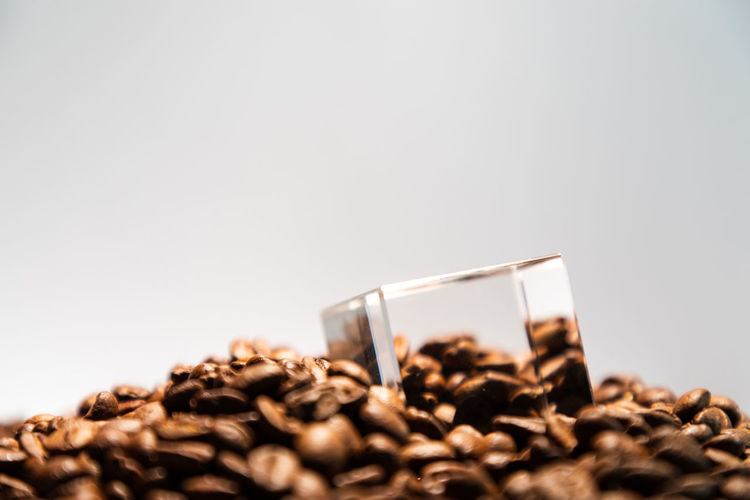 glass cube inside of some coffee beans Cube Brown Close-up Coffee Coffee - Drink Copy Space Drink Food Food And Drink Freshness Geometric Shape Geometry Glass Heap Indoors  No People Refreshment Roasted Coffee Bean Selective Focus Still Life Studio Shot Sweet Food Temptation Transparent White Background