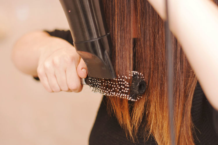 Midsection of woman combing hair