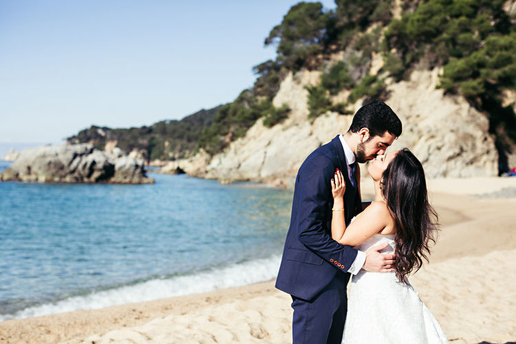 Newlywed couple kissing at beach against clear sky during sunny day
