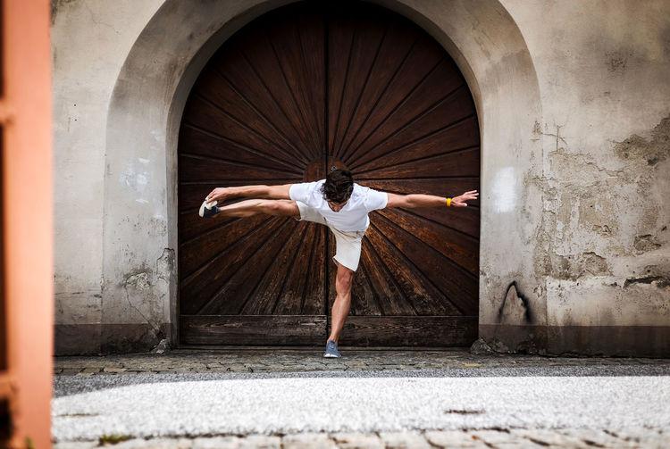 Young man exercising against door