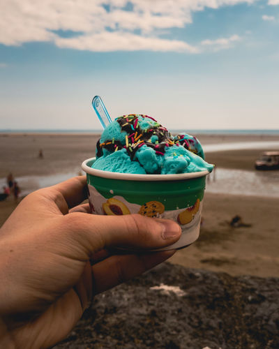 Close-up of person holding ice cream on beach