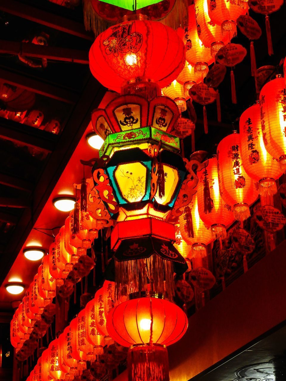 LOW ANGLE VIEW OF ILLUMINATED LANTERNS HANGING ON CEILING OUTSIDE BUILDING