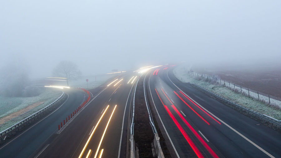 High angle view of light trails on foggy autobahn