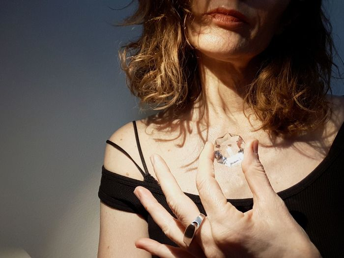 Midsection of woman holding diamond