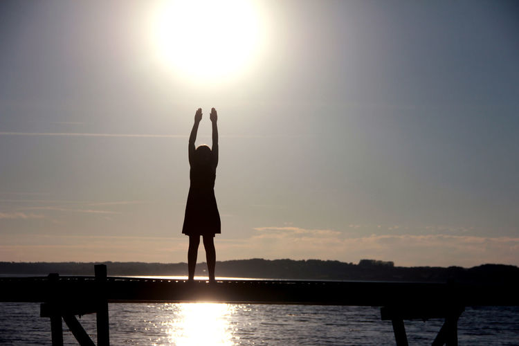 Denmark Arms Raised Beauty In Nature Girl Human Arm Leisure Activity Lens Flare Lifestyles Nature One Person Outdoors Real People Scenics - Nature Silhouette Sky Standing Sun Sunlight Sunset Tranquil Scene Tranquility Water