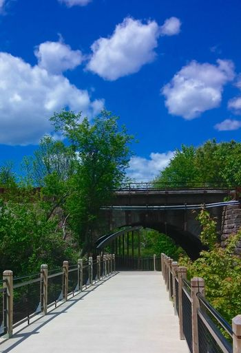 Sidewalk View Boardwalk Over The Wet Marsh Train Tracks Train Bridge Tunnel Stone Under The Train  Blue Sky Puffy Clouds Trees And Bushes Park Path