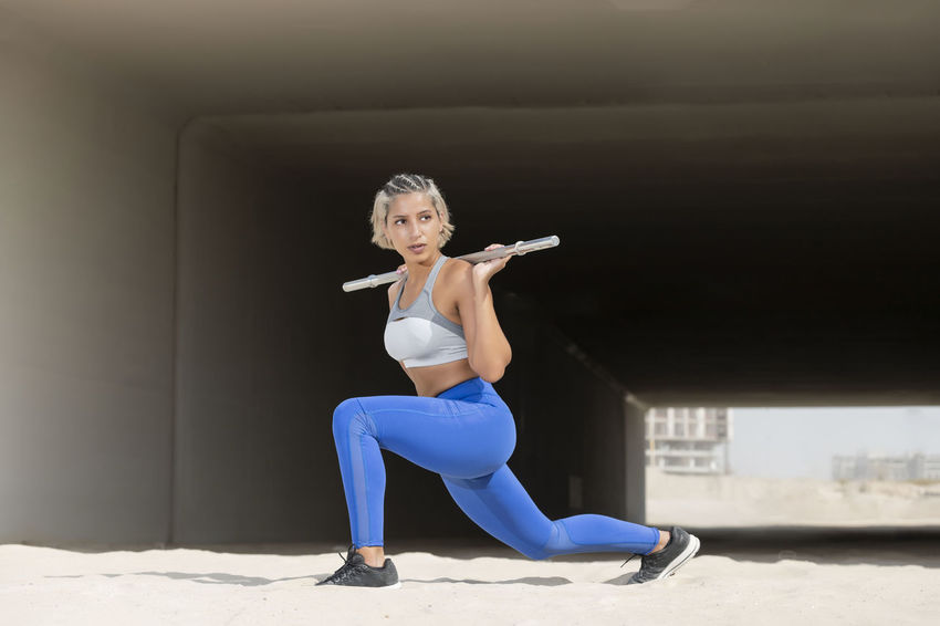 Middle Eastern Girl with short braided hair exercising in a urban setting with a tunnel in the back ground wearing blue and gray fitness outfit on a hot bright sunny day. Exercising Jumping Off Rocks Sitting Adult Beautiful Woman Blue Bright Day Concentration Dusty Exercising Fitness Model Front View Full Length Healthy Lifestyle Hot Day ☀ Leisure Activity Lifestyles Middle Eastern Woman One Person Real People Sport Sports Clothing Strength Stretching Wellbeing Women Young Adult Young Women