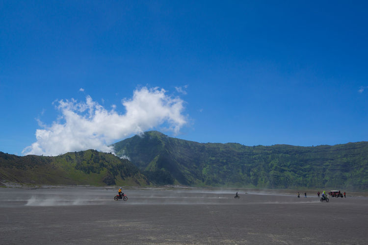People riding motorcycle on land against blue sky