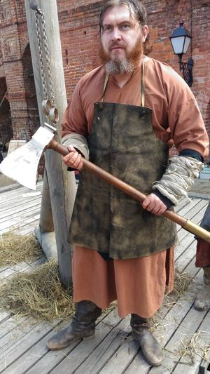 Man in traditional clothing holding axe while standing at farm