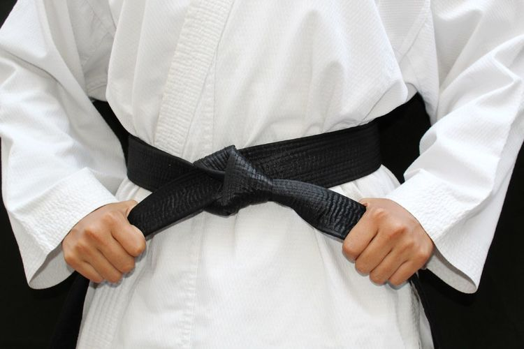 Midsection of athlete wearing black belt against black background