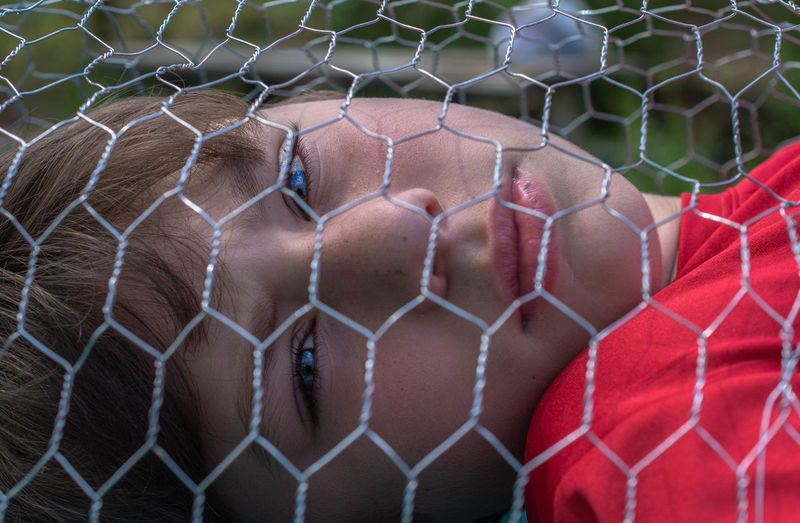Close-up of a boy behind a chainlink fence