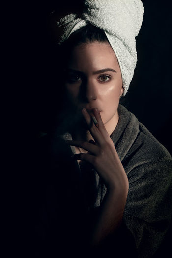 Portrait of young woman holding black background
