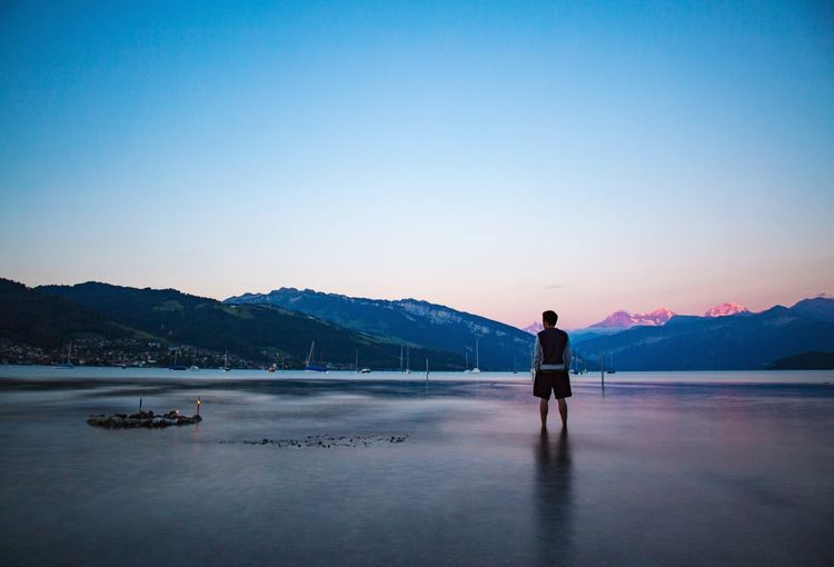 Rear view of man standing in lake against clear sky during dusk