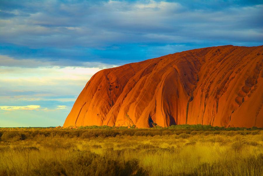 Aboriginal Land Ayer's Rock. Rock Uluru Uluru-Kata Tjuta National Park Beauty In Nature Cloud - Sky Day Field Grass Landscape Nature No People Orange Color Outdoors Scenics Sky Tranquil Scene Travel Destination AI Now