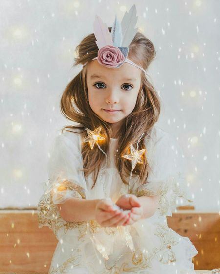 Portrait of girl wearing princess costume holding illuminated star shape