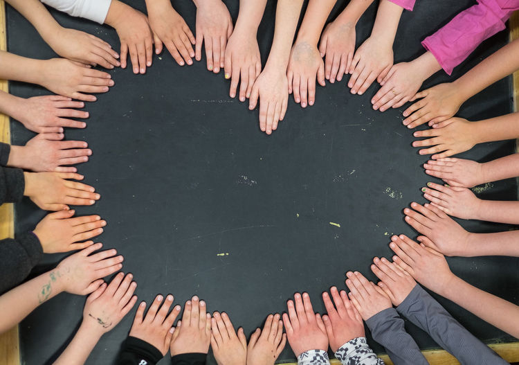 High angle view of people making heart shape from hands