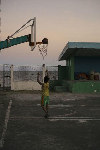 Rear view of man standing on basketball hoop