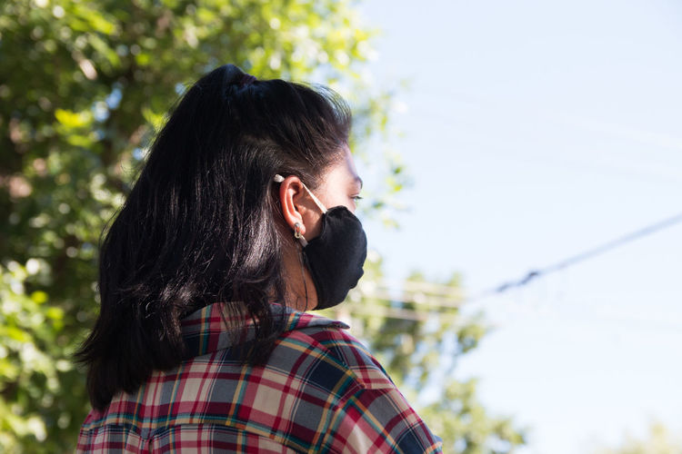 Back portrait of young woman wearing surgical face mask