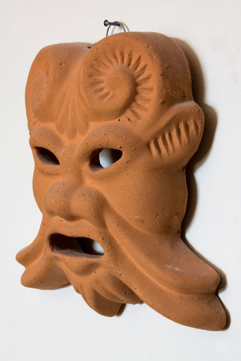Ocher and brown terracotta ancient mask hanging on white background Actor Ancient Antique Ceramic Mask Model? Dioniso Faun Close-up Expression Face Mask Horn Mask On Wall Museum Orange Mask Popular Art Profane Art Profanity Art Religion Satyr Sculpture Single Object Spirituality Statue Studio Shot Three Quarter Angle White Background