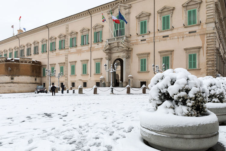 Rome, Italy - February 26, 2018: An exceptional weather event causes a cold and cold air across Europe, including Italy. Snow comes in the capital, covering streets and monuments of a white white coat. In the photo, Piazza del Quirinale, home of the President of the Republic. City Government Institutional Buildings President Quirinale Building Exterior Flag Governmental Headquarters Italian Flag Palace Quirinal Republic Residence Snow Snow Covered Snowing Symbolic  White