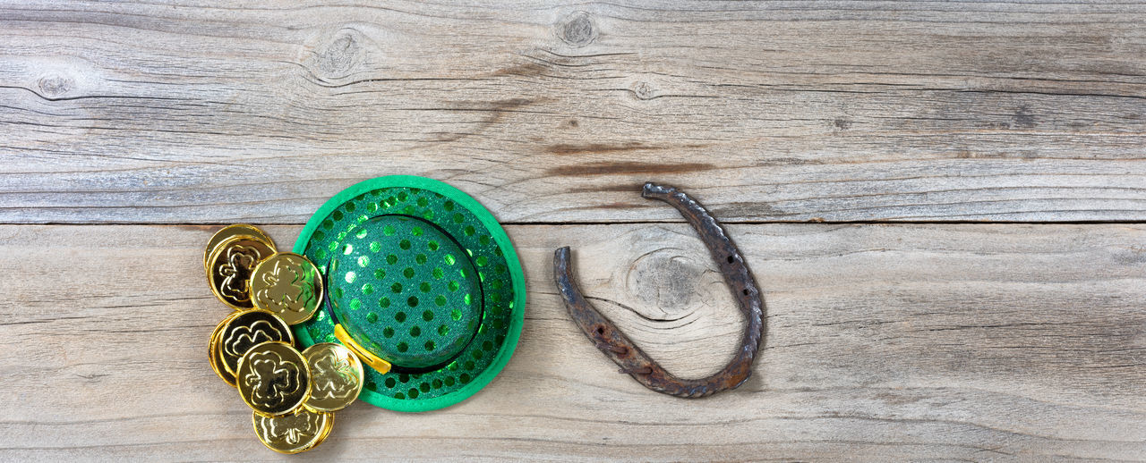Lucky green hat, horseshoe and gold coins for St Patrick on rustic wooden boards in overhead view Copy Space Gold Hat Holiday Horseshoe Luck St Patrick's Day Wood Coin Irish St Patrick