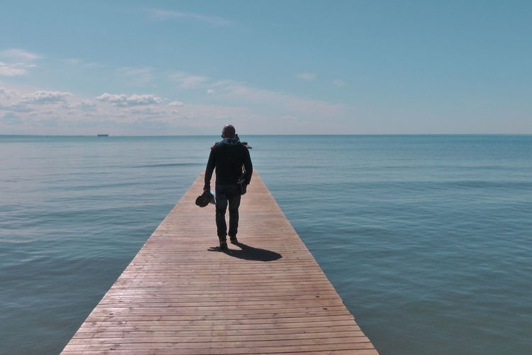 Rear view of man on pier over sea against sky