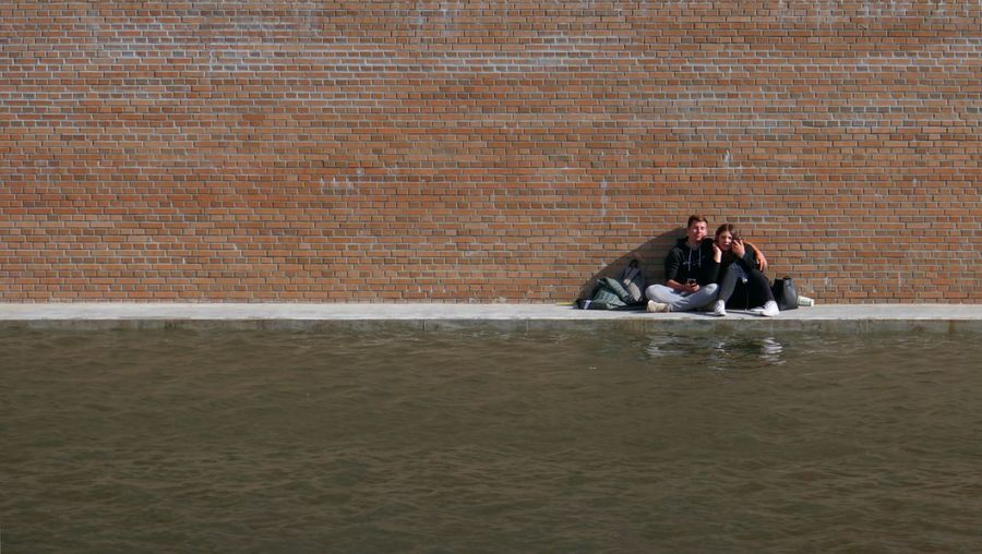 People sitting on wall by water