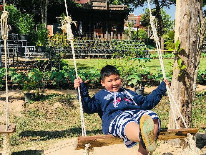 Portrait of smiling boy sitting on swing at park