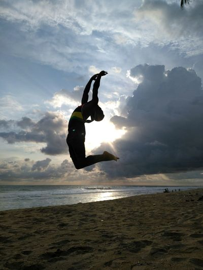 Woman jumping at beach against sky during sunset
