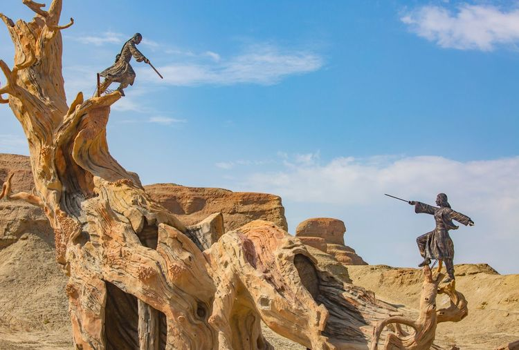 Low angle view of statues on bare tree at desert against sky