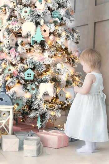 Side view of girl standing by christmas tree at home
