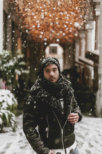 Portrait of man standing in snow against illuminated lighting equipment outdoors