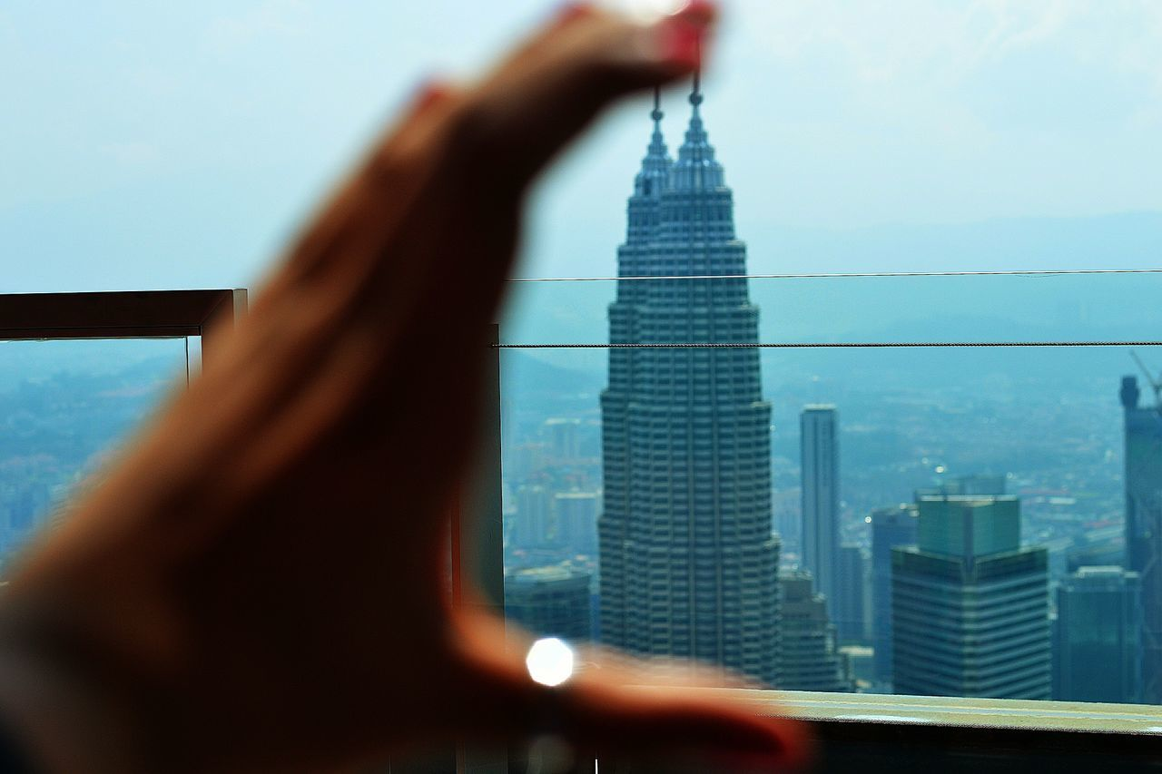 Optical illusion of cropped hand holding petronas towers in city