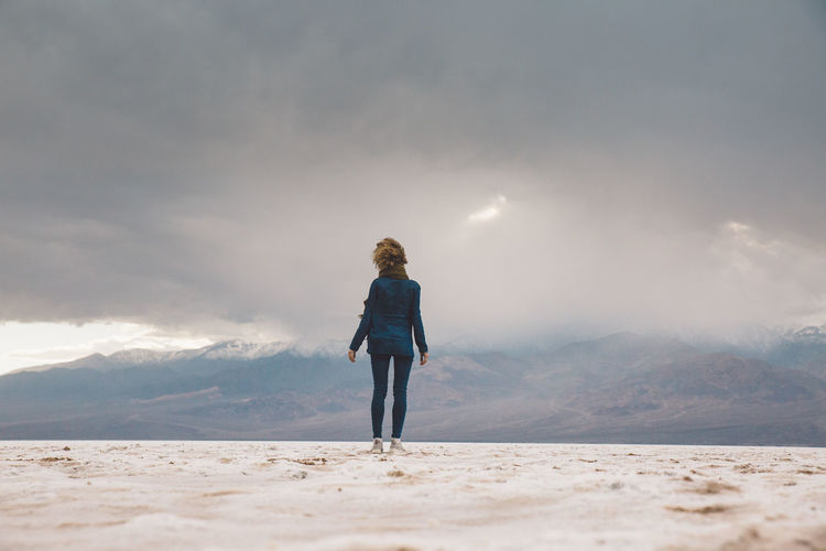Rear view of woman standing on snow covered land against sky