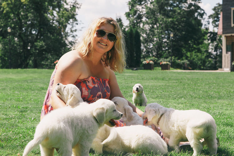 Portrait of happy mid adult woman sitting with puppies on grass at yard