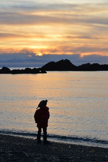 Winter on the beach. Coat Hat Kids Children Pondering Peaceful Colors Of Nature Sunset_collection PNW Anacortes Sunset Beach Water One Person Outdoors Sea Tranquility Silhouette Nature Vacations Beauty In Nature Landscape Full Length Adventure Sky People Travel Destinations