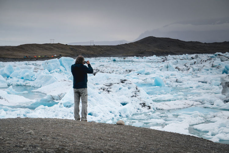 A man takes a photo of the ice on the lagoon at Jokulsarlon, Iceland. Adult Adventure Beauty In Nature Camera - Photographic Equipment Cold Temperature Day Digital Camera Full Length Glacier Ice Iceland Jökulsárlón Landscape Nature One Person Only Men Outdoors People Photographer Photographing Photography Themes Sky Snow Warm Clothing Winter