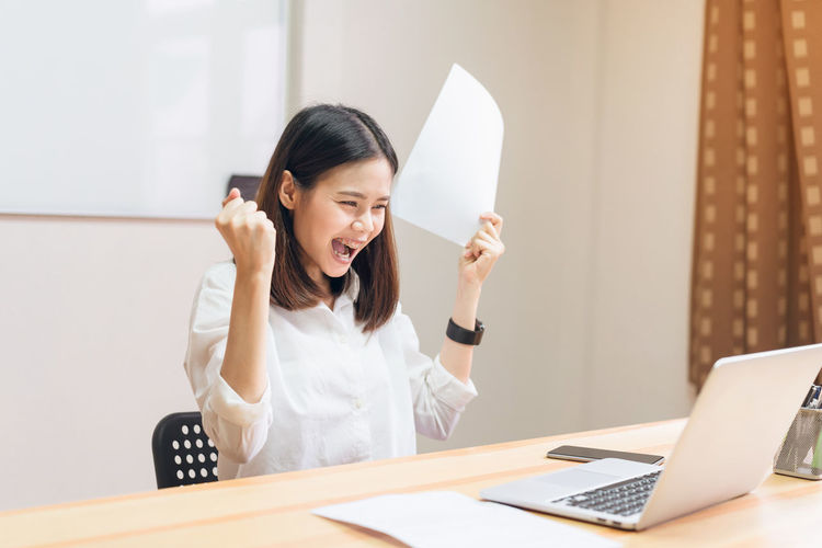 Happy Businesswoman Screaming While Looking At Laptop On Desk In Office