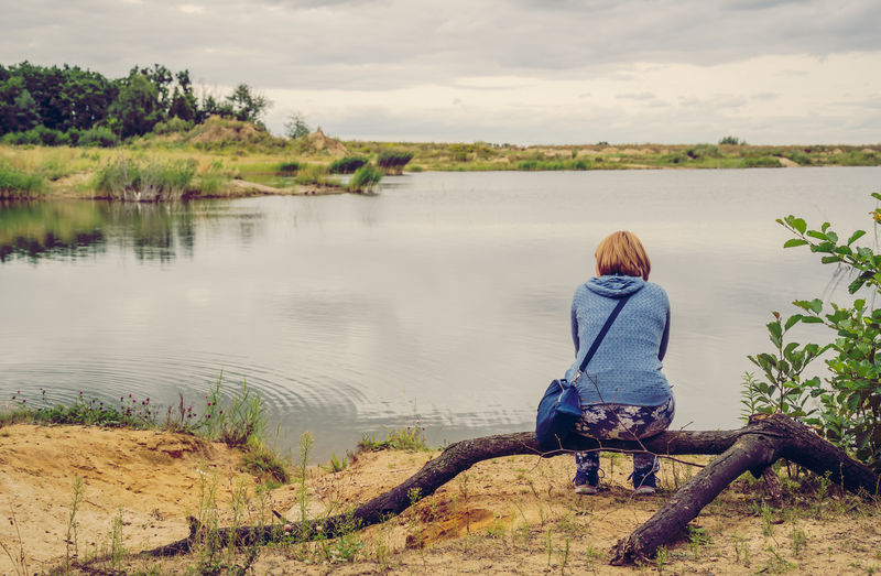 Rear view of woman looking at lake against sky