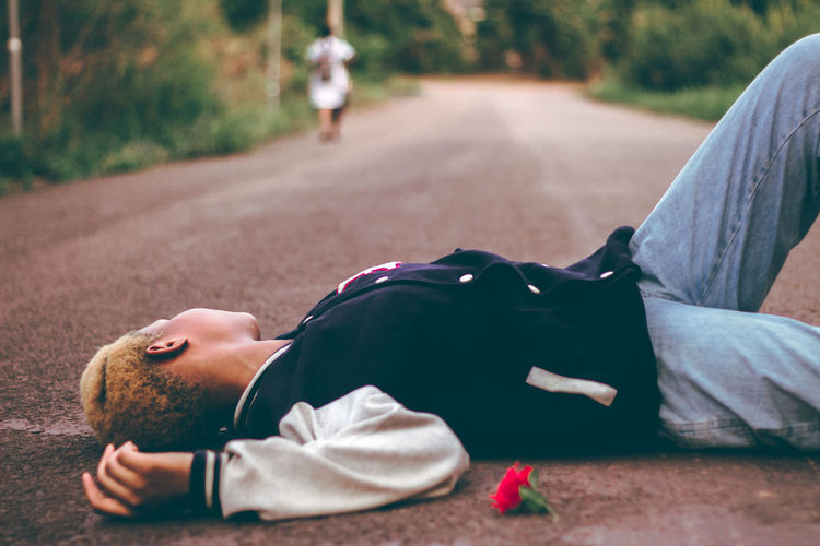 Side view of woman lying on road