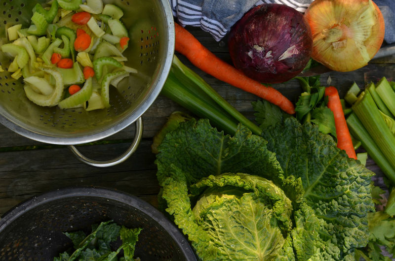 overhead view of savoy cabbage, celery, carrots, collanders Cabbage Close-up Collander Cooking At Home Day Food Food And Drink Food Preparation Freshness Healthy Eating No People Preparing Food Raw Food Savoy Cabbage Variation Vegetable Vegetables