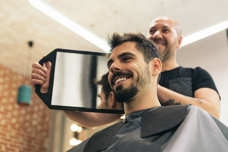 Low angle view of barber cutting man hair in salon