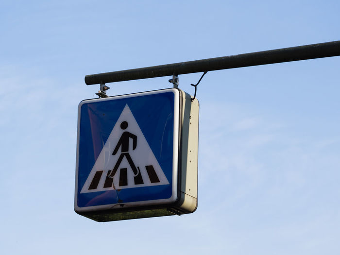 Low angle view of pedestrian crossing road sign against sky