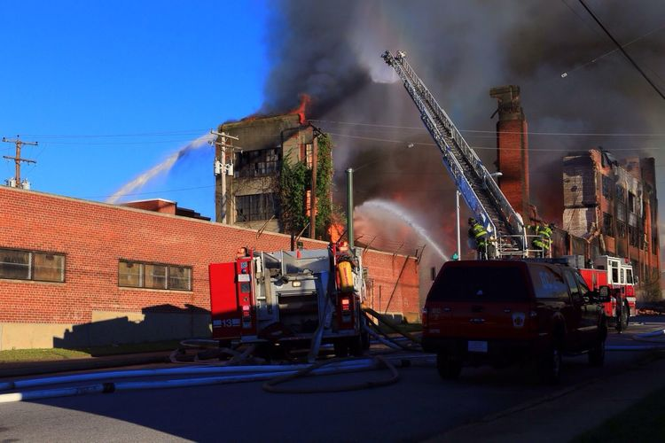 Rear view of firefighters working on street