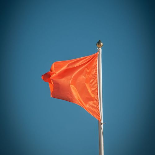 Low angle view of orange flag against blue sky