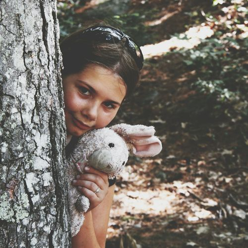 Girl Holding Bunny Toy While Hiding Behind Tree Trunk