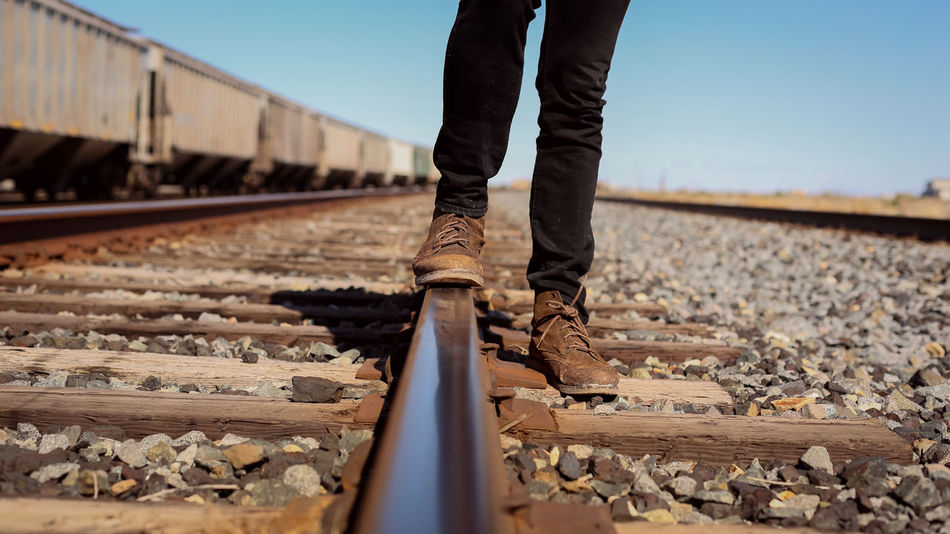 Trail Rail - Clear Sky Day Human Body Part Low Section One Person Outdoors People Rail Transportation Railroad Tie Railroad Track Real People Sky Standing Train - Vehicle Transportation Public Transportation