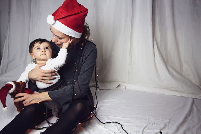 baby and mom at christmas time White Background Christmastime Mother Light Strings Two People Love Emotion Togetherness Positive Emotion Hat Christmas Family Indoors  Childhood Celebration Happiness Holiday Santa Hat Bonding